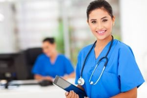 attractive young female nurse holding tablet computer at workplace