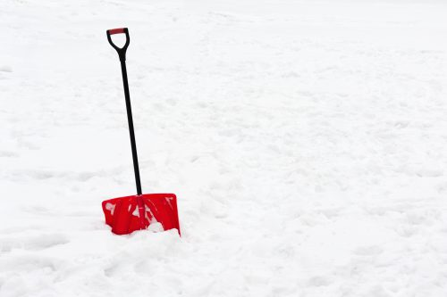 Red plastic shovel with black handle stuck in fluffy white snow.