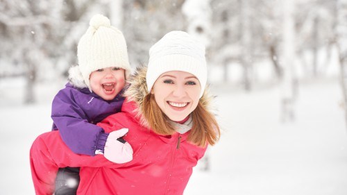 happy family mother and baby girl daughter playing and laughing in winter outdoors in the snow