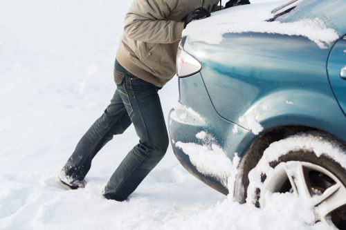 transportation, winter and vehicle concept - closeup of man pushing car stuck in snow