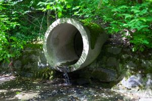 The concrete circular run-off pipe discharging water