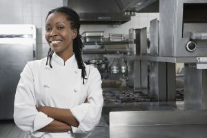 Portrait of a smiling female chef with hands crossed in the kitchen